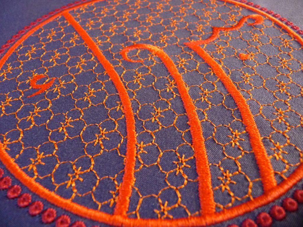 Stickerei arabische Schrift Mabruk, Glückwunsch, rot-orange auf violettem Hintergrund