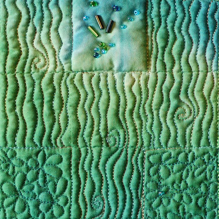 Miniquilt grüm mit verschiedenen welligen und blumigen Mustern und Perlenstickerei