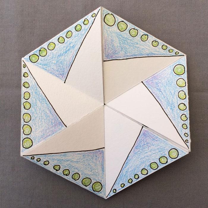 Ein Papier-Flexagon bemalt mit blauen Dreiecken und grünen Punkten, als Wirbel