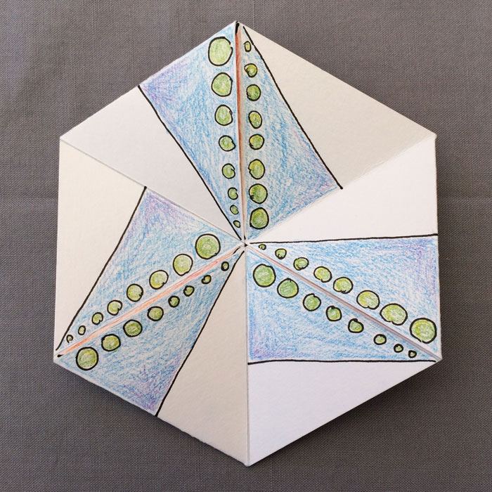 Ein Papier-Flexagon bemalt mit blauen Dreiecken und grünen Punkten, als Rechtecke