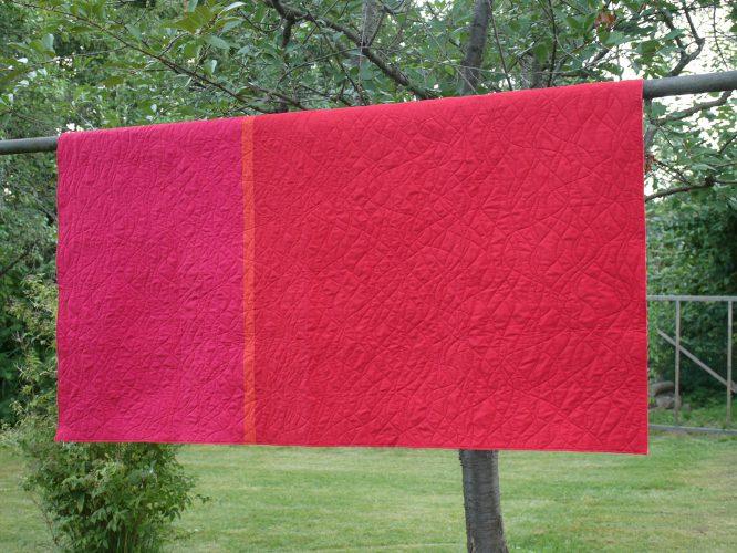 Quilt rot und pink mit welligen Linien, in verschiedenen Garnfarben, im Garten