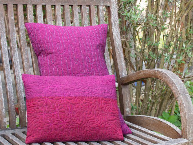 zwei Kissen in beerenfarben auf einer alten Gartenbank