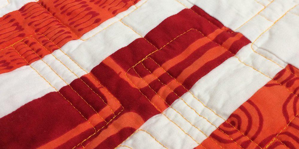 weißer Quilt mit rot-orangen Streifen